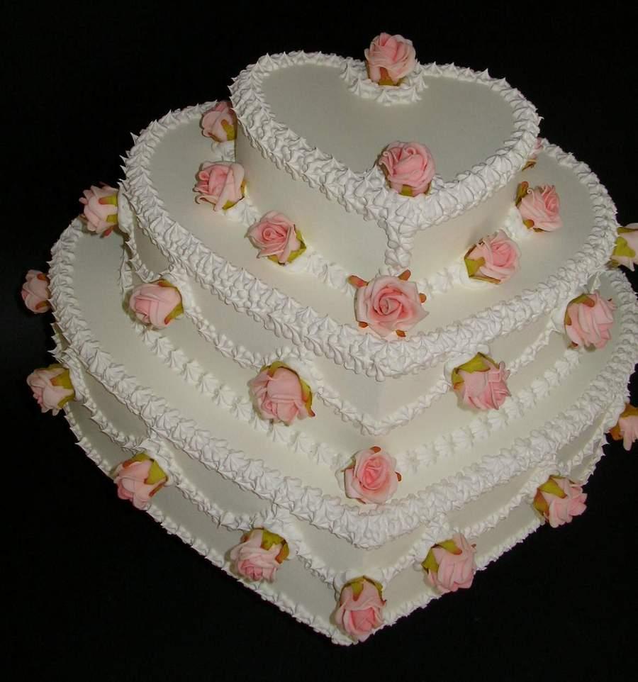 torta matrimoniale a cuore, tre piani, con roselline rosa