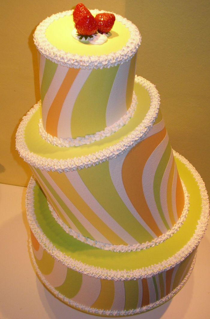 torta a tre piani con decorazioni geometriche, panna e fragole