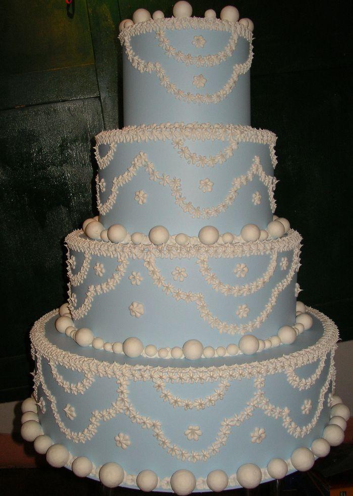 torta azzurra a 4 piani con bon bon bianchi