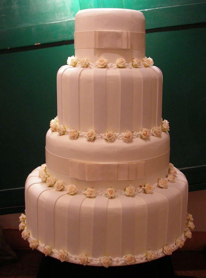 Importante torta a 4 piani con roselline e fiocchi