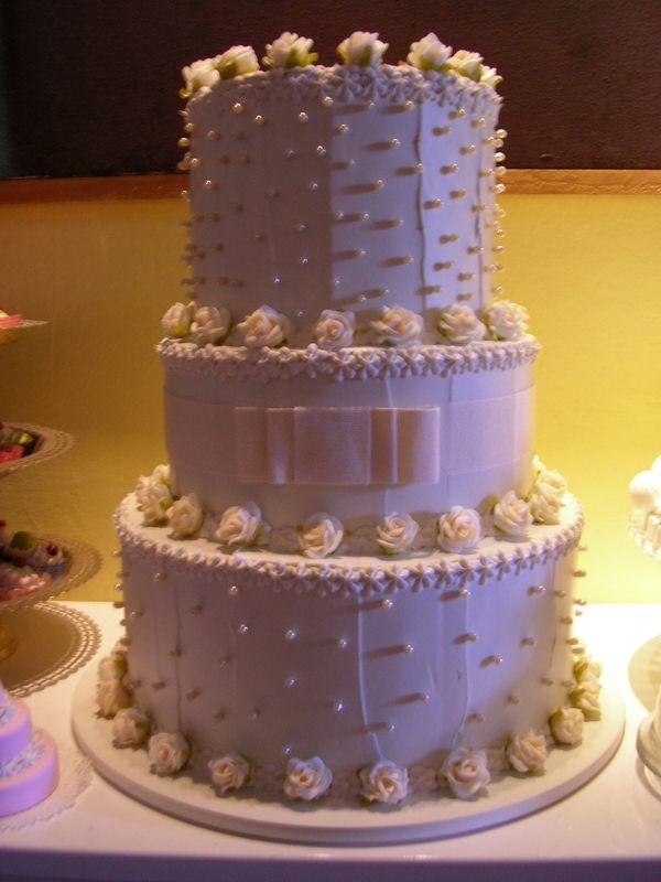 torta 3 piani bianca con roselline crema e fiocco