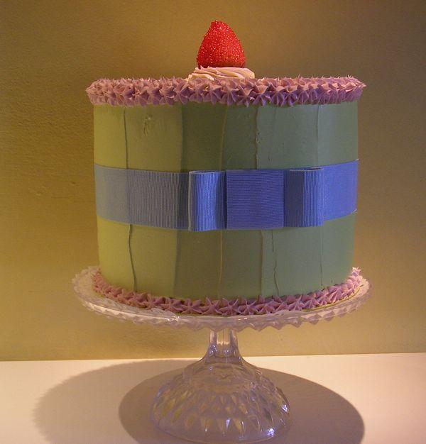 torta verde acido con panna rosa, nastro azzurro e fragola