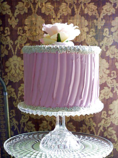 torta rosa chiaro con panna e rosa