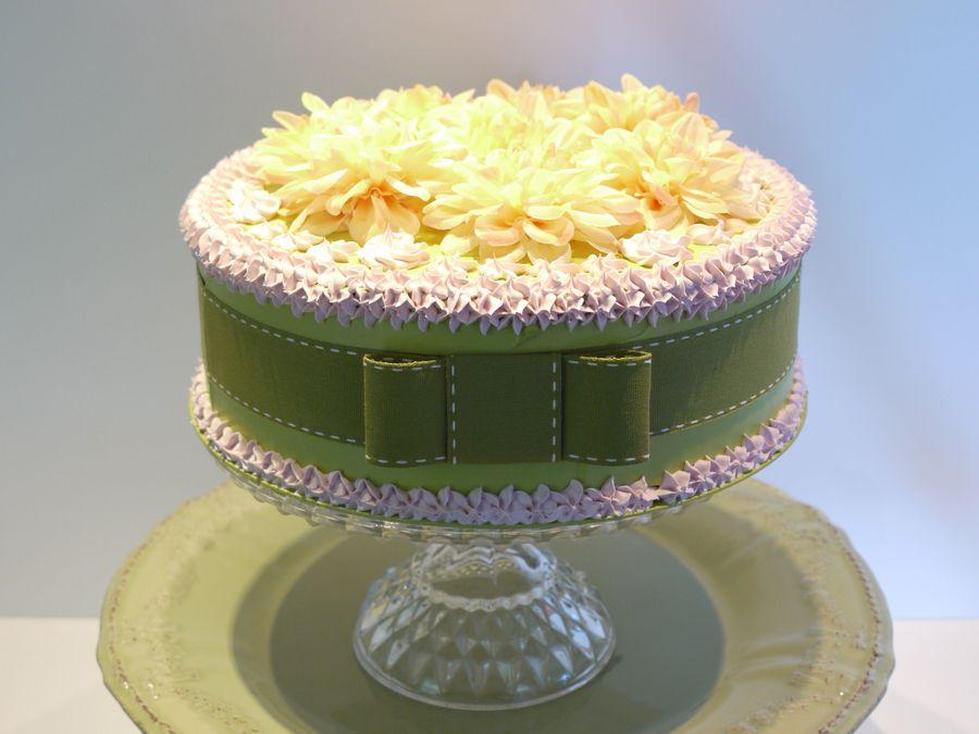 Torta verde acido, panna rosa, nastro verde e fiori